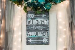 All of Me Loves All of You. Wedding details that speak to the theme of true love. This is a rustic and simplistic wedding detail that speaks to a white and blue Stock Photo