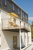 All metal balcony. An image of a balcony constructed using aluminium supported on steel pillars and with a wooden rocking chair placed on it stock images