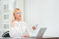 All in the mind.Businesswoman in glasses holding a pen near the Royalty Free Stock Photos