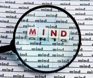 All in the mind. Text 'mind' in uppercase red letters inscribed on small white cubes viewed through a magnifying glass and seen against a background of 'mind' stock photos