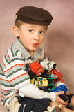 All Mine. Young boy with all his toy cars in his arms royalty free stock photography