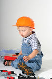 All my tools. Cute toddler boy wearing an orange hard-hat inspecting his play tools Stock Photos
