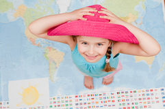 All my world. Little girl standing at world map background stock photo