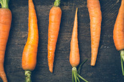 All-natural carrots lined up on wooden board Royalty Free Stock Photos