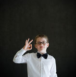 All ok or okay boy dressed up as business man. All ok or okay sign boy dressed up as business man, teacher or student on blackboard background Royalty Free Stock Image