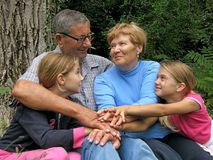 All for one. Portrait of  group of people of different generations - clasped hands - happy grandparents take with hands (close up) granddaughters on summer Royalty Free Stock Photo
