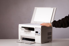 All-in-one. Man's hand with working copier Royalty Free Stock Images