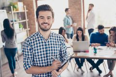 All for one and one for all! Leadership. Successful stylish young bearded man in casual checkered shirt is standing in the office. All for one and one for all! stock images