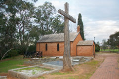 All Saints Church: Rustic Cross. HENLEY BROOK,WA,AUSTRALIA-JULY 15,2016: All Saints Church historic building with cemetery and large rustic wooden cross in treed Royalty Free Stock Photos