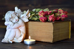 All Saints Day theme. Angel, burning candle, bunch of dry roses and old book Stock Images