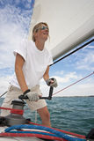 All At Sea. Shot of beautiful young woman on the deck of a boat operating a winch to hoist a sail Royalty Free Stock Photos