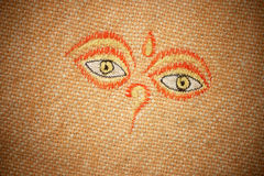 The all-seeing eyes of Buddha on canvas texture. Royalty Free Stock Image