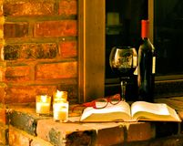 All set to read and relax. Book,wine and glasses left sitting by the fireplace while owner went to get cheese and crackers Royalty Free Stock Photo