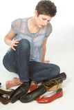 All this shoes on sale!. Young woman sitting on the floor tries to choose pair of shoes Stock Images