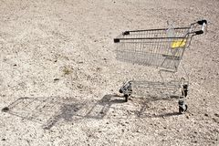 All sold out. Empty shopping cart on gravel surface royalty free stock images