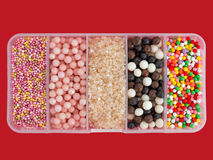 Assorted cake sugar decorations - sprinkles isolated over red Royalty Free Stock Photos
