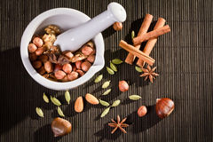 All sorts of nuts in white mortar. On wooden table Stock Photo