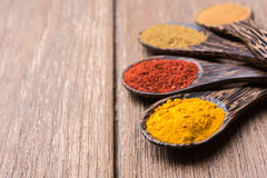 All spice powder on the spoon. On the wooden table stock photos