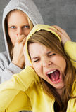 All stinks and makes noise. Portrait of two teenage girls, one is holding her nose, the other screams and holding her ears. Symbolic studio shot against a gray Stock Photography
