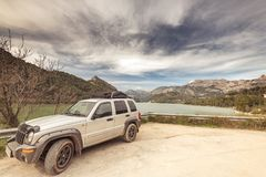 All terain car by lake in mountains,road trip concept. Stock Image