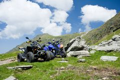All terrain vehicles offroad on mountain. Image of all terrain vehicles (ATV) on a rocky mountain in a sunny day with blue sky and fluffy clouds. Holiday and Stock Images