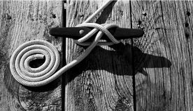 All Tied Up. Black and white of a boat tie in Morehead City, NC. Coiled rope and rough boards give it nice texture Stock Photo