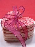 All tied up heart sugar cookies. Heart shaped sugar cookies stacked and tied with ribbon. Cookies on a white plate with red background Royalty Free Stock Photo