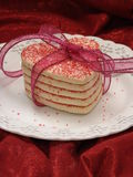 All tied up heart sugar cookies. Heart shaped sugar cookies stacked and tied with ribbon. Cookies on a white plate with red background Stock Photography
