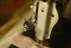 All Tied Up on a Sewing Machine. Depiction of an old sewing machine head, with its metal chrome and white thread weaving its way through its many connecting Royalty Free Stock Images