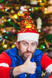 Man with beard in  New Year cap with spiral. All is well. Portrait of a man with a beard in a cheerful cap with a spiral raised his thumb up. Back decorated Royalty Free Stock Images