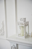 All white. White lantern with a candle standing on the mantelpiece white. All white. White lantern with a candle standing on the mantelpiece white Royalty Free Stock Photo