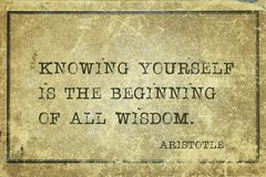 All wisdom Aristotle. Knowing yourself is the beginning of all wisdom - ancient Greek philosopher Aristotle quote printed on grunge vintage cardboard royalty free stock image