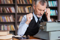 That is all wrong!. Frustrated grey hair senior man in formalwear sitting at the typewriter and holding pieces of paper in his hands with bookshelf in the Stock Photo