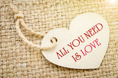 All you need is love. All you need is love on brown paper price tags Heart shapes with brown rope on sack background. Recycled paper Stock Image