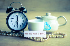 All you need is love concept. Vintage all you need is love and alarm clock with set bowl coffee on wooden background Stock Photography