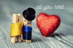 All you need is love invitation card. Romantic clothespin characters. Gentleman in black hat and woman in gold dress. Red heart background. Creative design Royalty Free Stock Photography