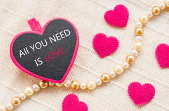 All you need is love. Love concept. All you need is love on pink heart wooden clamps and on fabric background Stock Images