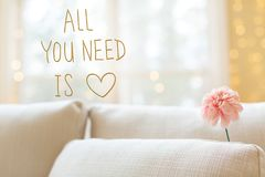 All You Need Is Love message with flower in interior room sofa stock photo
