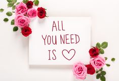 All You Need Is Love message with roses and leaves. Top view flat lay stock photo