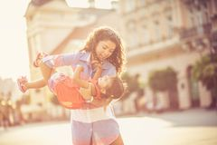 All you need is mom to make you smile. Single mother playing with her daughter on city street. Copy space royalty free stock images