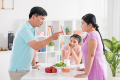 This is all your fault!. Image of middle-aged parents quarreling at breakfast within sight of their teenage daughter on the foreground stock photo