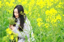 Alla bella molla in anticipo, un supporto della giovane donna in mezzo ai fiori gialli della violenza ha archivato che è il più g fotografia stock