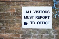 Alla besökare måste anmäla till kontorstecknet på arbetsplatsen arkivbild