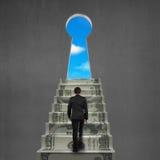 Alla cima delle scale dei soldi con il foro chiave ed il cielo Fotografie Stock