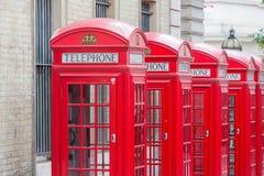 Alla fem röda London telefonaskar i rad Arkivfoton