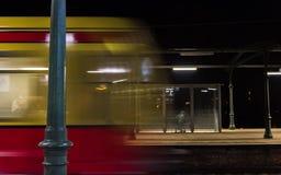 Alla notte in cui il treno rosso giallo arriva fotografia stock
