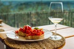 Alla Pomodore di Bruschete con il vetro di vino del ehite Fotografia Stock
