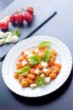 Alla Sorrentina van aardappelgnocchi in tomatensaus met groene verse basilicum en mozarellaballen diende op een plaat stock afbeelding