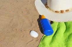 Alla spiaggia, al cappellino da sole, all'asciugamano e al sunmilk Fotografia Stock