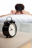 Allarm clock with sleepy Asian girl Stock Image